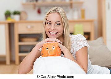 Beautiful woman with a piggy bank - Conceptual image of a...