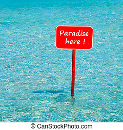 turquoise tropical sea with red sign saying Paradise here -...