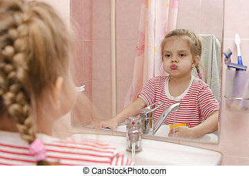 Four-year-old girl rinse teeth after cleaning in bathroom