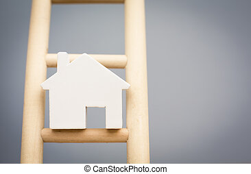 Model Houses On Rung Of Wooden Property Ladder