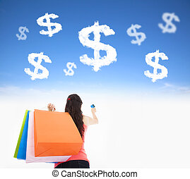 young woman holding shopping bags and credit card with money cloud