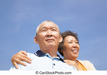 Happy elderly seniors couple with cloud background