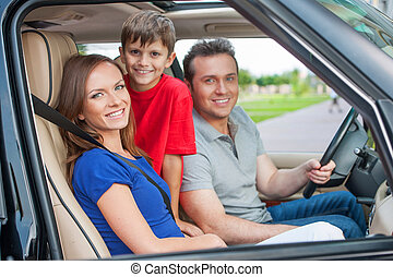 Family with one kid is traveling by car, smiling and looking...