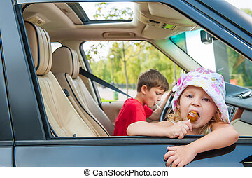 Two kids is going by car without parents Girl eats candy,...