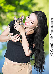 Young smiling brunette posing with a funny little dog
