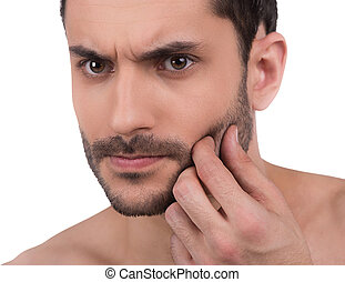 Close up of man's unshaven face - Man touches his skin