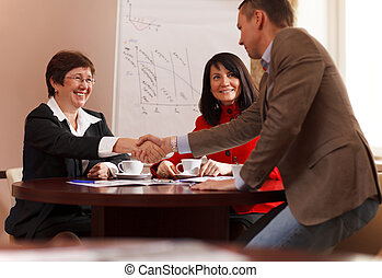 Business man and woman shaking hands - Businessman rising to...