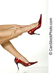 Beautiful legs in red shoes isolated on white background