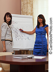 Businesswoman giving a presentation standing in front of a...