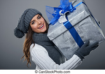 Happy woman wearing warm clothing holding big present
