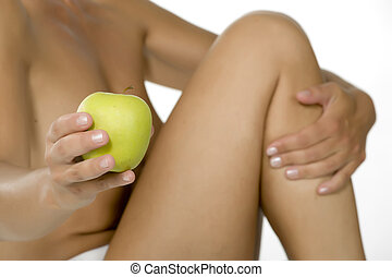 Apple on the belly of beautiful woman isolated on white...