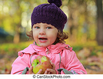 Funny kid girl eating apple on bright autumn background