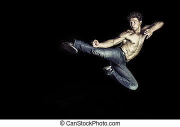Martial art athlete doing the kick jumping