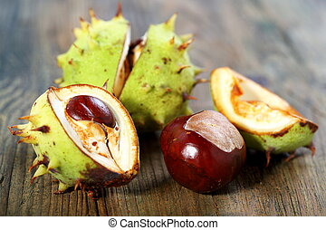 Ripe chestnuts. - Ripe chestnuts on an old wooden board.