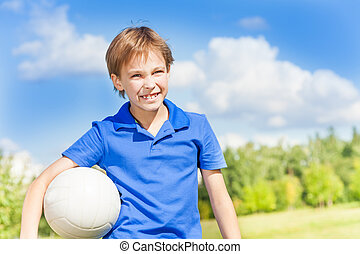 I love volleyball - Nice smiling happy 8 years old boy stand...