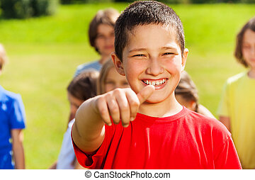 All right - Close portrait of happy Asian boy showing thumb...