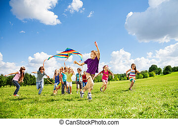 Kite is fun for friends - Kids boys and girls with kite run...