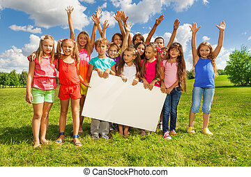 Group of kids with placecard - Many boys and girls holding...