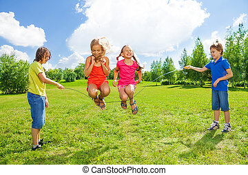 Girls jumping over the rope with friends - Two girls jumping...