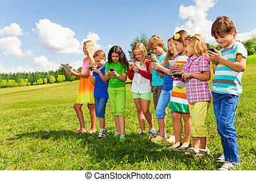 Group of kids with phones - Large group of busy kids, boys...