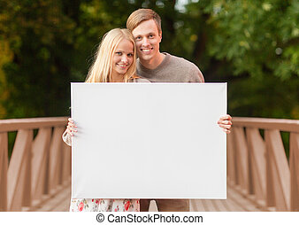 romantic couple with blank white board - summer holidays,...