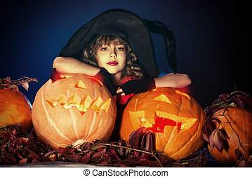 smiling pumpkins - Little girl in a costume of witch posing...