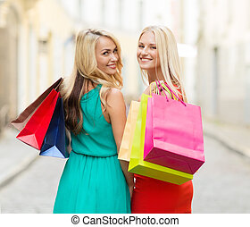 beautiful women with shopping bags in the city - sale and...