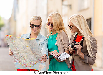beautiful women with tourist map in the city - holidays and...