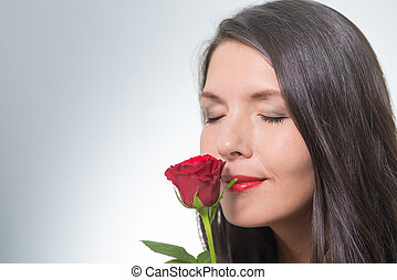 attractive woman smells on a long-stemmed red rose -...