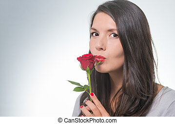attractive woman holding a long-stemmed red rose -...