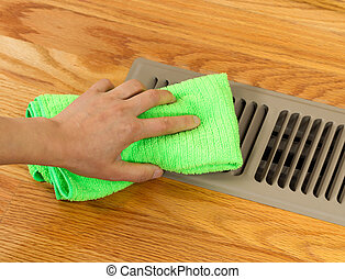 Hand Cleaning Grill Plate of Floor Heating Vent in Home