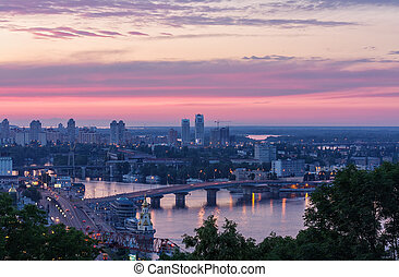 The view of the Dnieper river and bridge in Kyiv at sunset -...