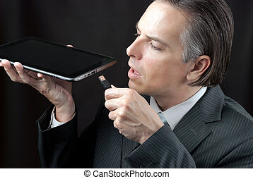Businessman Plugs In Tablet - Close-up of a businessman...