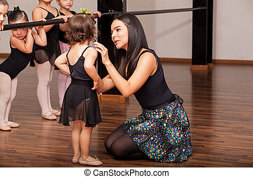 Teacher comforting a dance student - Young female dance...