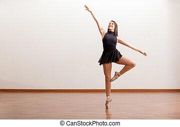 Happy ballet dancer in a studio