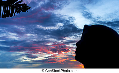 veiled woman silhoutte with orange skies