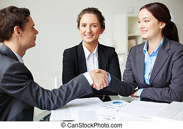Agreement - Portrait of business partners handshaking on...
