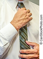 man fixing a tie with hands