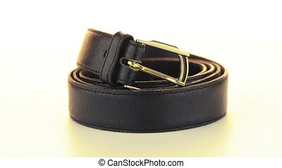 Leather belt rotating on white background.