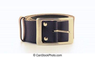 Leather belt rotating on white background.