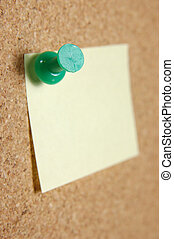 Close up of pushpin with post-it note on corkboard