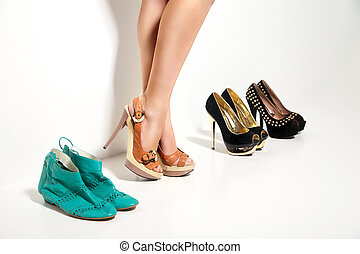 Womans legs and many shoes over white background
