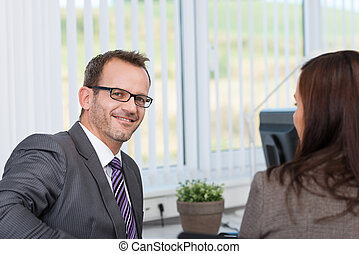 Businessman in a discussion with a colleague - Smiling...