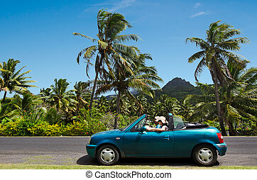 Couple traveling by convertible car in a Pacific Island -...