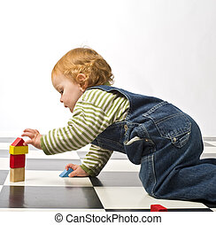 little boy playing with building blocks on a checkered floor