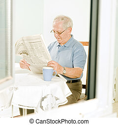 senior reading a newspaper - senior man reading a newspaper...