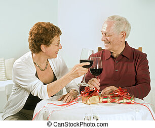 senior couple having a glass of wine - senior couple having...