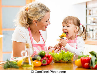 mother feeding kid daughter vegetables in kitchen