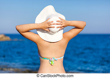 A woman in hat is posing