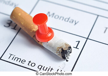 Quit smoking - Cigarette butt impaled on calendar